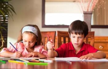 kids doing homework at kitchen table