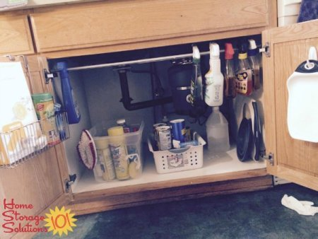 Use a tension rod under your kitchen sink to hang spray bottles for easy organization {featured on Home Storage Solutions 101}