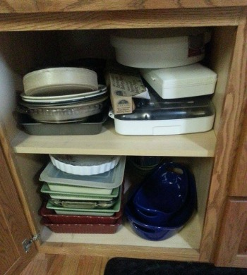 stacked bakeware in cabinet