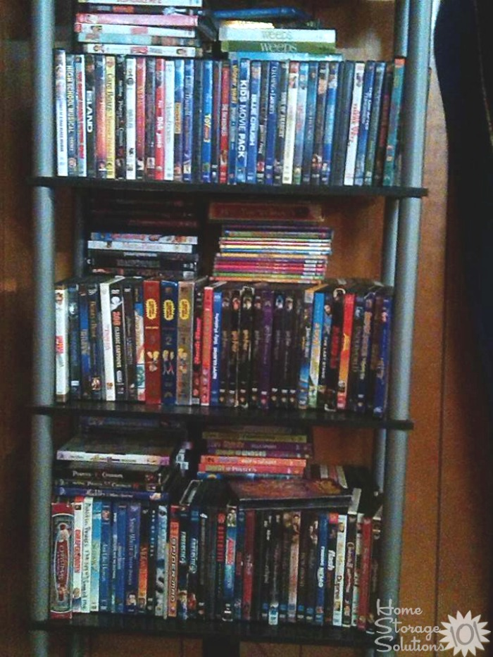 Cluttered bookshelf with excess DVDs that needs to be decluttered {featured on Home Storage Solutions}