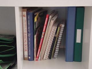 Organized cookbooks and recipe binders on shelf