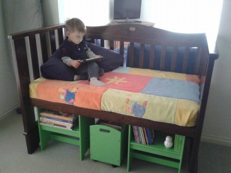 repurposed baby crib turned into reading nook