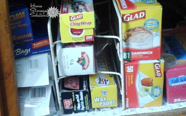 Store aluminum foil and kitchen wrap boxes in a simple rack in the pantry {featured on Home Storage Solutions 101}