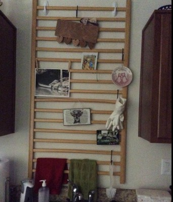 used baby crib rail hung in kitchen